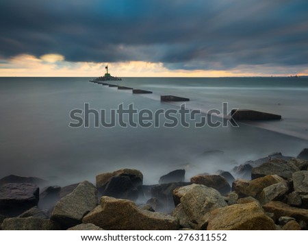 Mouth of the river Vistula in Gdansk. Long exposure seascape. Beautiful rocky breakwater on sea shore and protection walls on mouth of river. - stock photo