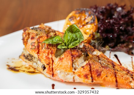Mouthwatering fried fish cooked with vegetables. Beautiful feed fish on a white plate. Professional kitchen. Photo for culinary magazines and websites.
