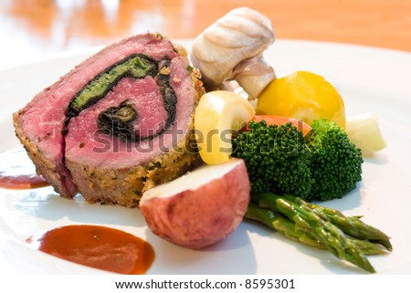 Mouthwatering platter of beef steaks served with mushrooms, red potato, asparagus, broccoli, lime wedge and steak sauce. - stock photo