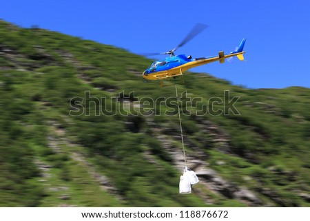 movement of goods in the mountains by helicopter on the background with  motion blur