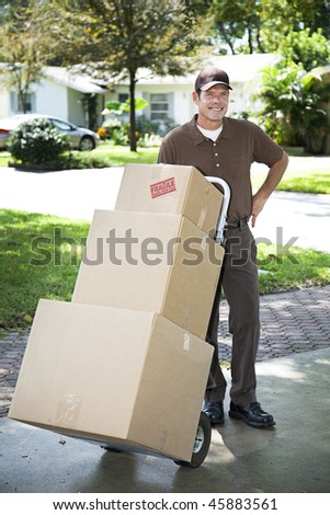 Mover or delivery man arrives with a stack of boxes for you. - stock photo