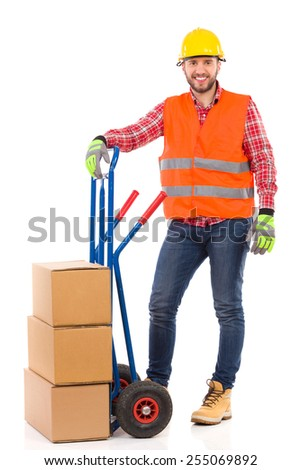 Mover. Smiling man in yellow hardhat and orange reflective vest posing with a delivery cart and looking at camera. Full length studio shot isolated on white. - stock photo