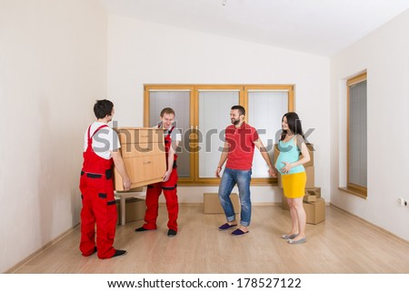 Movers in new house with young family - stock photo