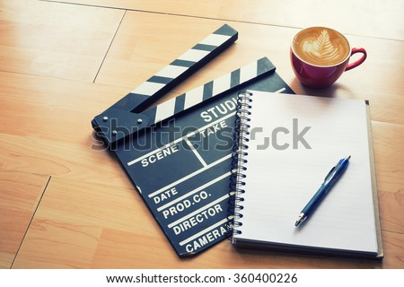 Movie clapper and Notepad with coffee on wood table,Vintage effect. - stock photo
