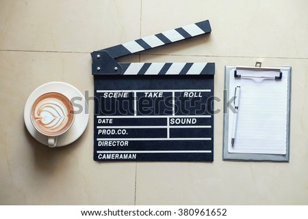 Movie clapper notepad and coffee of cup on office table.vintage effect  - stock photo