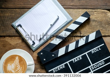 Movie clapper notepad and coffee of cup on wood table.  - stock photo