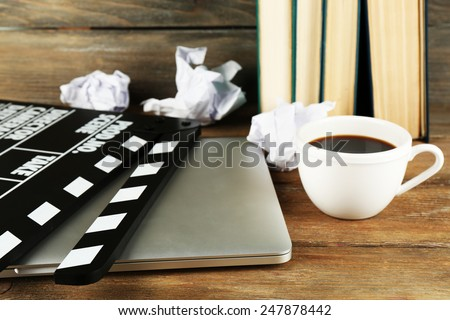 Movie clapper with laptop and cup of coffee on wooden background - stock photo