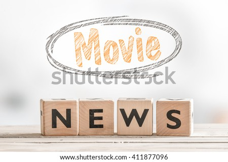 Movie news sign cubes on a table with a sketch - stock photo