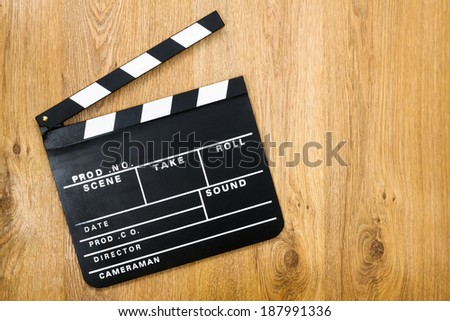 Movie production clapper board against wooden background with copy space - stock photo