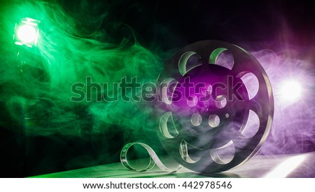 Movie reel of film in retro in the smoke of green and purple on a dark background - stock photo