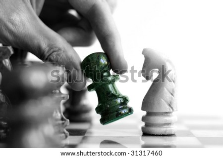 Moving a chess piece (in color) across the board - stock photo