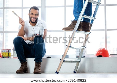 Moving and repairs in the apartment. Smiling worker painter sitting on a windowsill and holding a brush with paint while his friend standing in the background on a ladder in an empty apartment - stock photo