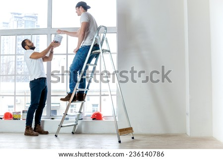 Moving and repairs in the apartment. Two workers make repairs in a new apartment. A Man takes the paint to another man on the ladder - stock photo