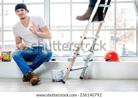 Moving and repairs in the apartment. Young painter man sitting on the window sill and keeps fingers okay while his friend standing in the background on a ladder in an empty apartment - stock photo
