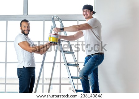 Moving and repairs in the apartment. Young worker man holding a paint can while his friend standing in the background on a ladder in an empty apartment - stock photo