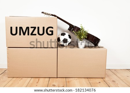 moving boxes, guitar, football and flower in a room - stock photo