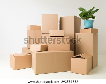 moving boxes stacked in empty room ready for movers - stock photo
