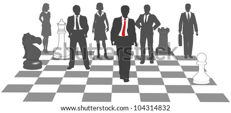 Moving business man leads team to win as pieces on chess board - stock photo