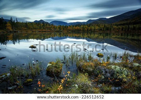 Moving clouds reflected in Polygonal freshwater lake at dusk in Hibiny mountains above the Arctic Circle, Russia - stock photo
