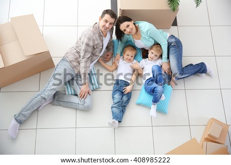 Moving concept. Happy family lying on floor among cardboard boxes, top view - stock photo