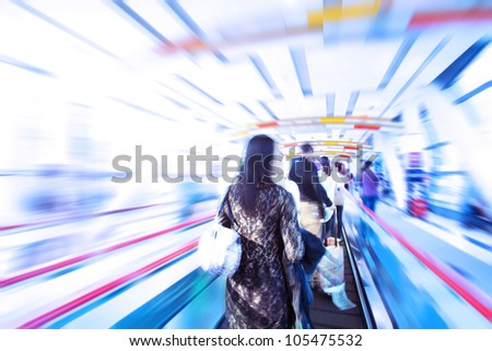 moving escalator with people in big mall - stock photo