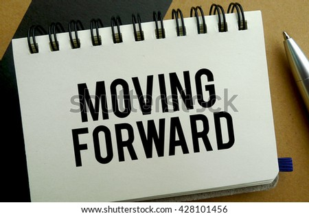 Moving forward memo written on a notebook with pen
