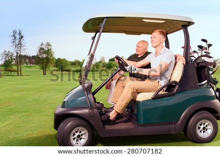 Moving forward. Side-draw of smiling old and young golf player driving cart on course. - stock photo