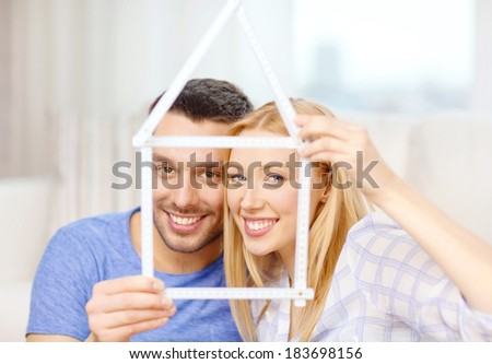 moving, home and couple concept - smiling couple with house from measuring tape at new home
