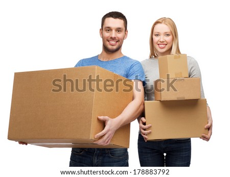 moving, home and family concept - smiling couple holding cardboard boxes - stock photo