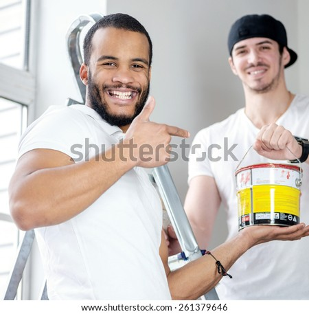 Moving in and renovation in an old apartment. Young worker man holding a paint can while his friend standing in the background on a ladder in an empty apartment - stock photo