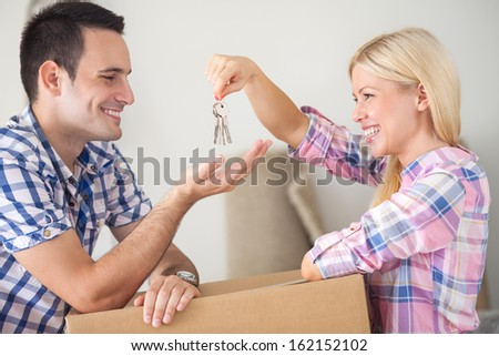 Moving into new home young happy couple, girl holding house keys and giving her boyfriend  - stock photo