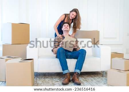 Moving joint, a new life. Couple in love enjoys a new apartment and keep the box in his hands while young and beautiful couple in love sitting on the couch in an empty apartment among boxes - stock photo