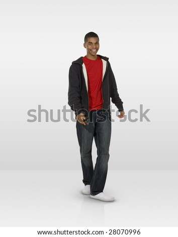 Moving male teen with mobile phone - stock photo