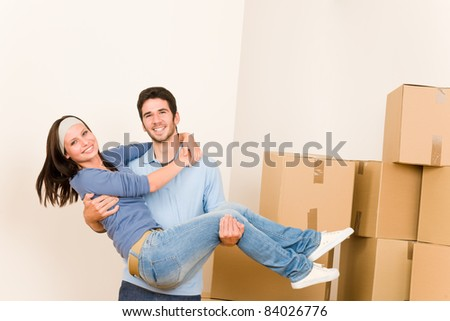 Moving new home young happy man holding woman cardboard boxes