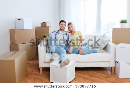 moving, people, repair and real estate concept - happy couple with big cardboard boxes on sofa at new home - stock photo