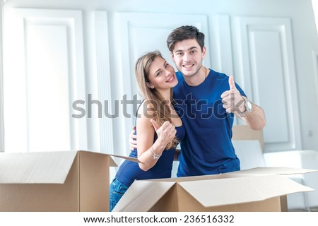 Moving, repairs, new flat. Couple in love pulls things out of boxes for moving and hug and show a thumbs up while man and woman are sitting among the boxes in an empty apartment