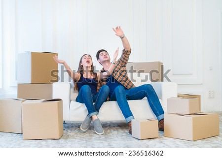 Moving, repairs, new life. Couple in love enjoys a new apartment and keep the box in his hands while young and beautiful couple in love sitting on the couch in an empty apartment among boxes - stock photo