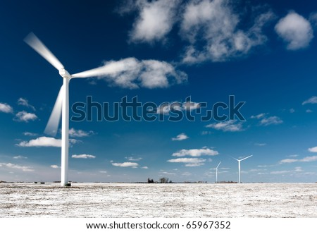 Moving wind turbine blades in snow covered winter field. - stock photo