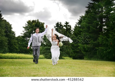 Moving young happy wedding pair against the storm sky