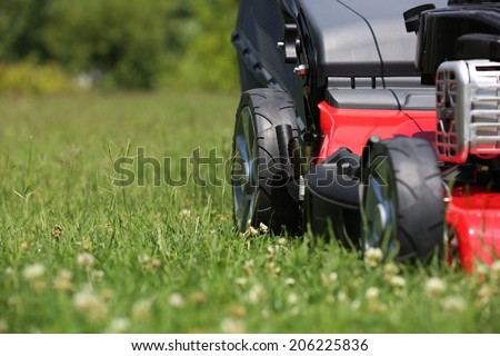 Mower  Lawn mower on the grass during the summer day - stock photo