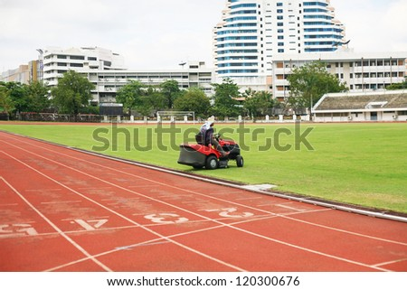 Mowing grass in a football stadium - stock photo