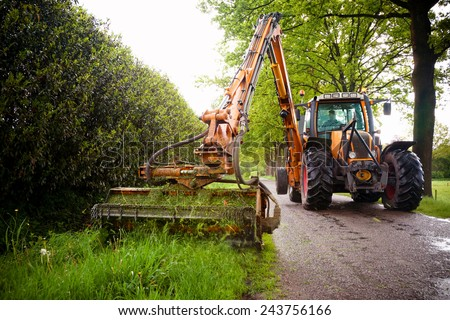 mowing grass shoulder along road in public space  with big orange tractor mower  - stock photo