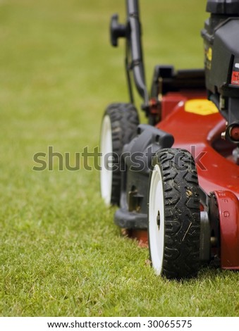 Mowing grass with my new lawnmower - stock photo