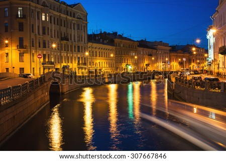 Moyka river in Saint Petersburg, Russia at night with a motion blurred touristic boat, illuminated old buildings, winter bridge and clear blue sky. Various bars and restaurants, lights reflection - stock photo