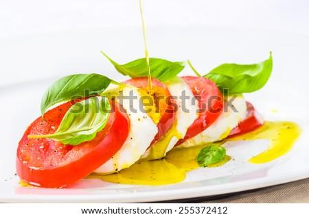 Mozzarella and tomatoes with basil, caprese salad.Restaurant menu plate closeup. - stock photo