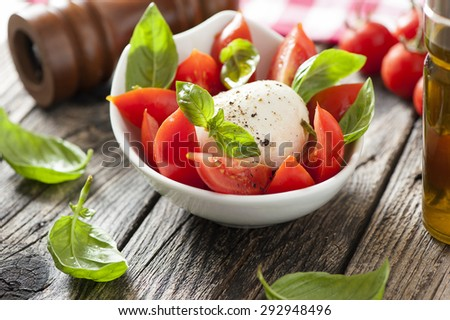 mozzarella cheese with basil and tomatoes in bowl, on wooden table - stock photo