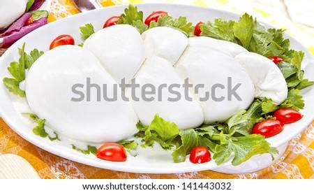 mozzarella on a green salad with tomatoes - stock photo