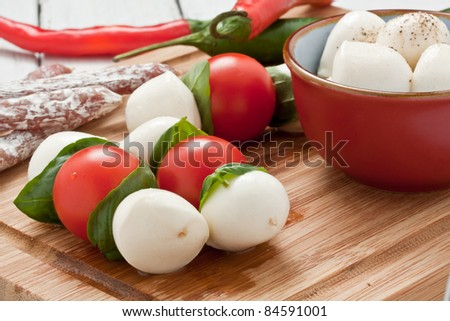 mozzarella skewers with tomato and basil - stock photo