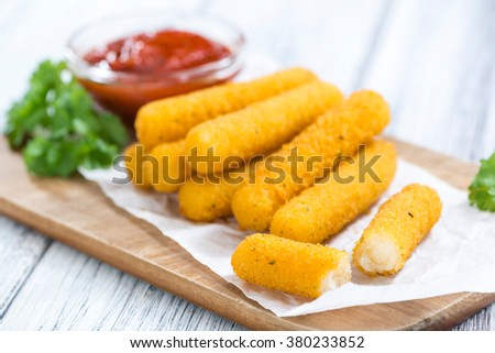 Mozzarella Sticks with a homemade dip on wooden background (selective focus) - stock photo