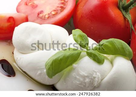Mozzarella tomatoes and fresh salad on the white - stock photo